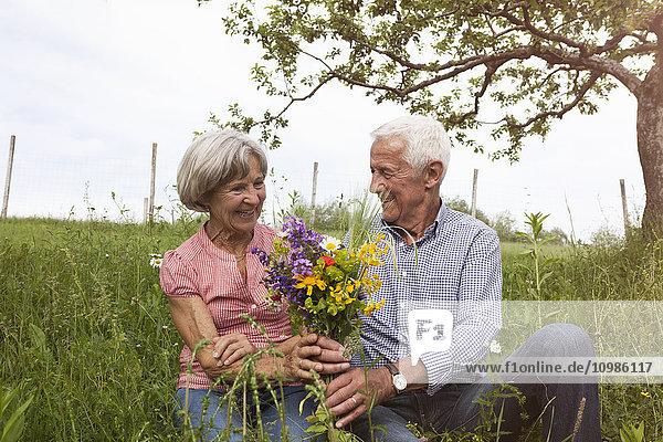 Glückliches Seniorenpaar mit Blumenstrauß auf der Wiese