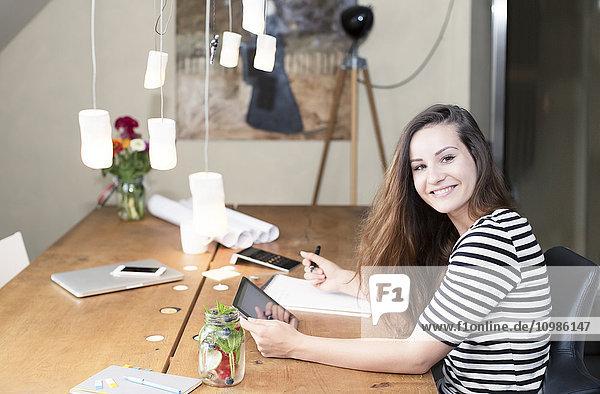 Porträt einer lächelnden jungen Frau mit digitalem Tablett