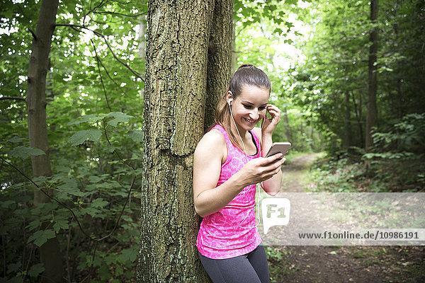 Sportliche junge Frau mit Smartphone und Ohrhörern