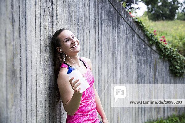 Fröhliche sportliche junge Frau mit Trinkflasche