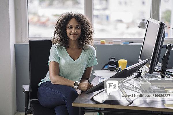 Junge Frau im Büro sitzend mit digitalen Tabletten  lächelnd