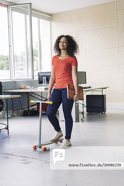 young woman carrying laptop  using kickboard in office
