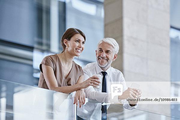 Geschäftsmann und Frau mit Kaffee und Handy