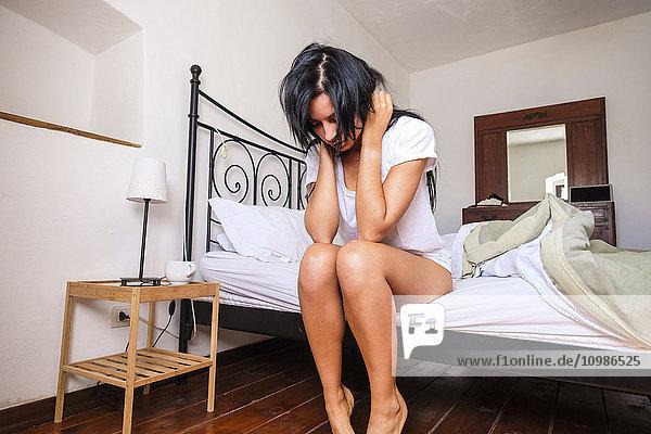 Frau auf dem Bett sitzend  aufwachend