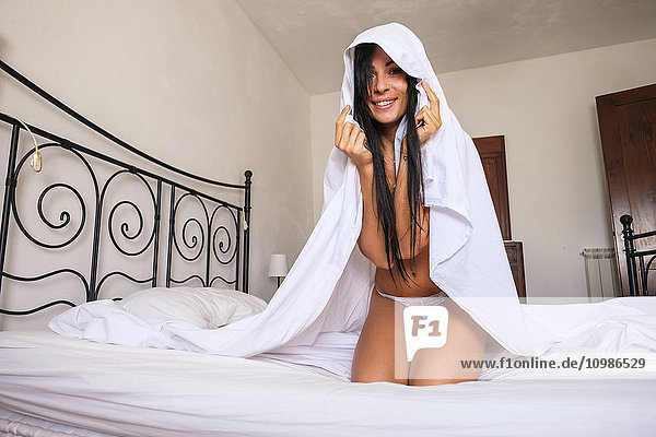 Italian woman under bed sheet  sitting on bed