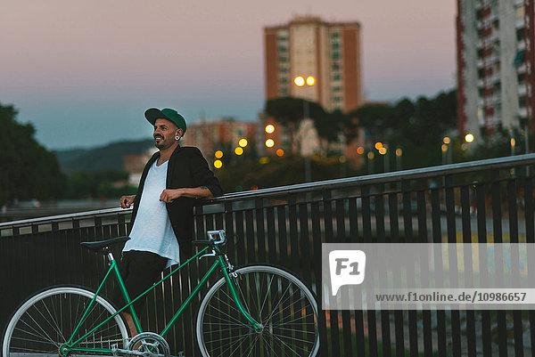 Lächelnder Mann mit Fahrrad an Geländer gelehnt in der Dämmerung