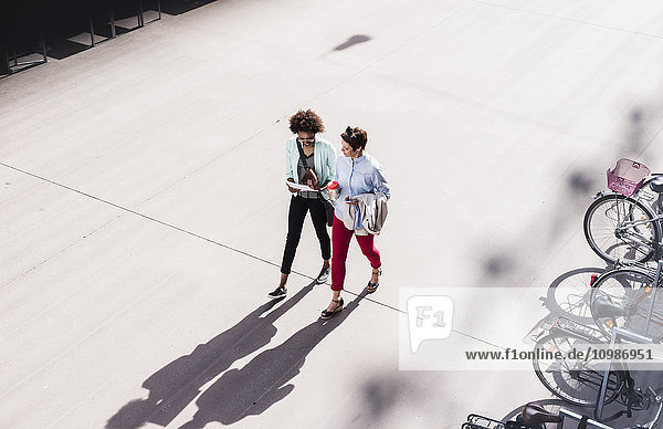 Two businesswomen walking and talking