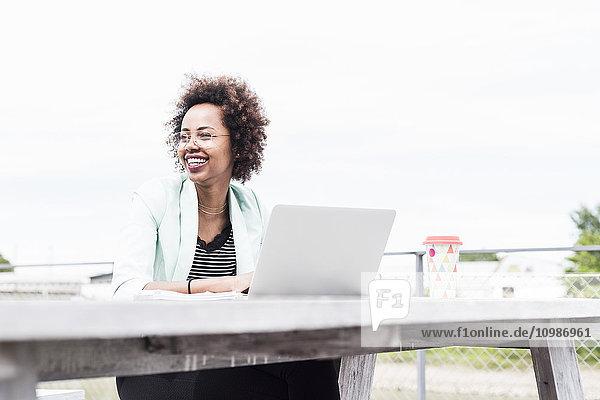 Lächelnde Geschäftsfrau  die draußen mit ihrem Laptop arbeitet.