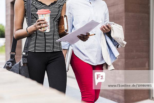 Zwei Geschäftsfrauen gehen Seite an Seite  Teilansicht