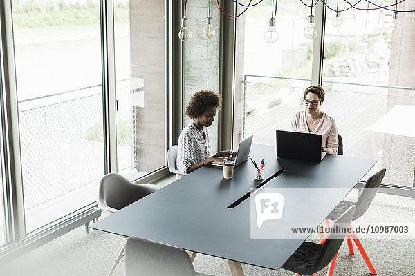 Zwei Frauen  die an Laptops in einem Büro arbeiten.
