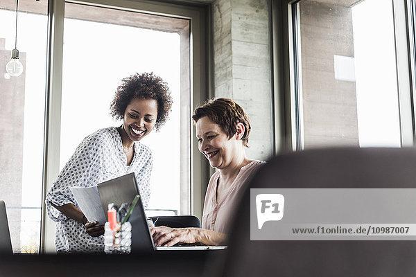 Zwei lächelnde Frauen  die zusammen in einem Büro arbeiten.