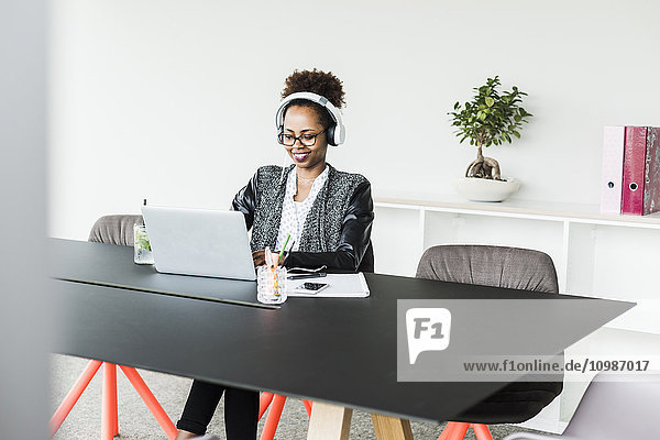 Geschäftsfrau mit Kopfhörer am Schreibtisch bei der Arbeit mit Laptop