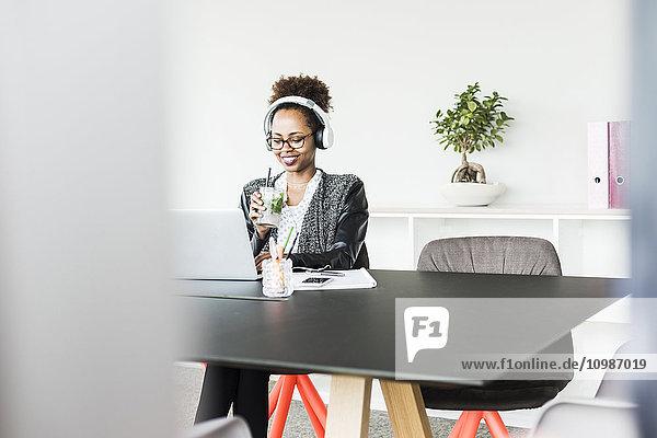 Geschäftsfrau mit Kopfhörer und Getränk am Schreibtisch sitzend mit Blick auf Laptop