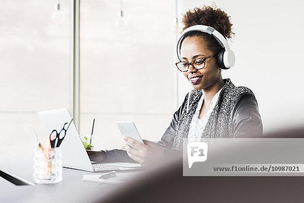Geschäftsfrau mit Kopfhörer am Schreibtisch und Blick aufs Handy