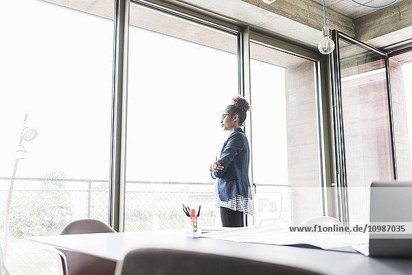 Junge Geschäftsfrau mit gekreuzten Armen steht im Vorstandszimmer und schaut durchs Fenster.