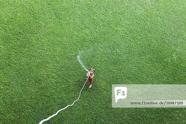 Kleiner Junge auf dem Rasen stehend mit Gartenschlauch  Draufsicht