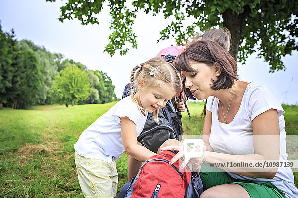 Mutter und Töchter beim Wandern  Blick in den Rucksack