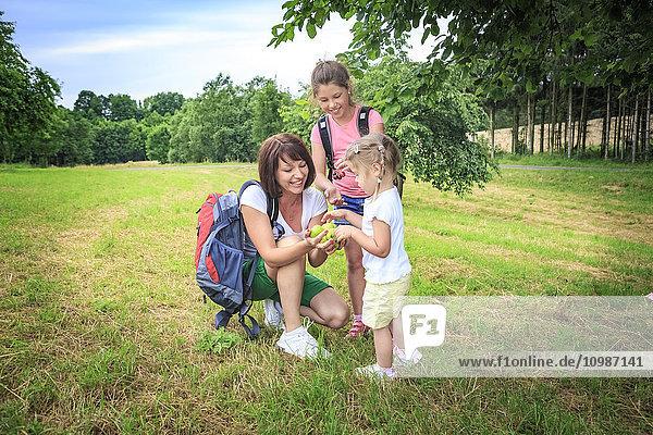 Mutter schenkt Äpfel  Mutter und Töchter auf der Wiese beim Wandern