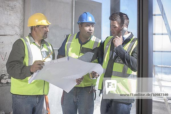 Architekt und Bauarbeiter diskutieren den Bauplan