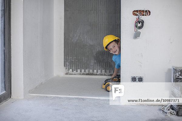 Glücklicher Junge mit Schutzhelm auf der Baustelle