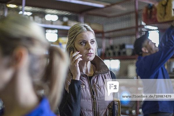 Frau in der Werkstatt am Telefon