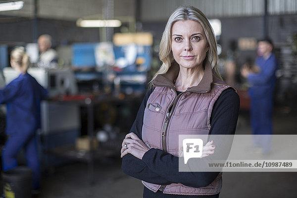Porträt einer selbstbewussten Frau in der Werkstatt