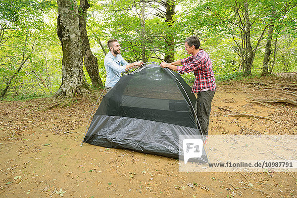 Friends putting up a tent at a camp site