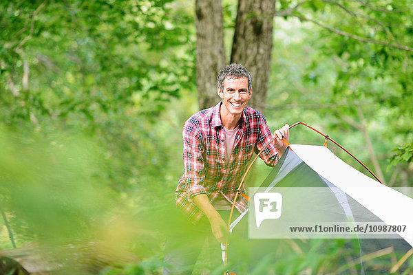 Caucasian man putting up a tent at a camp site