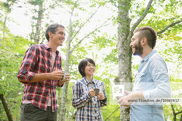 Multi-ethnic group of friends having coffee at a camp site