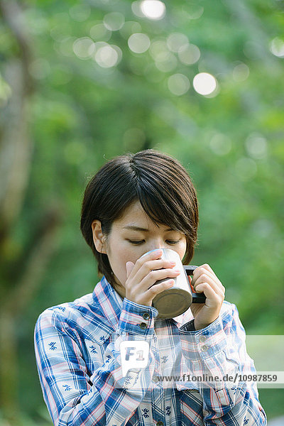 Young Japanese woman drinking coffee at a camp site