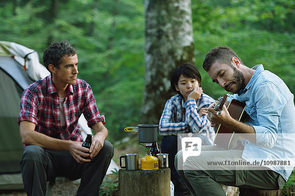 Multi-ethnic group of friends playing guitar at a camp site