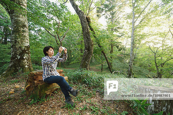 Young Japanese woman taking pictures at a camp site
