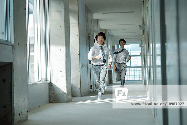 Japanese high-school students running in school corridor