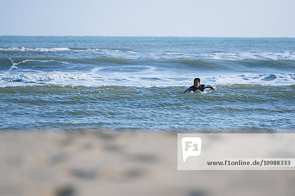 Japanese surfer paddling in the sea