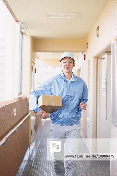 Young Japanese delivery man with box