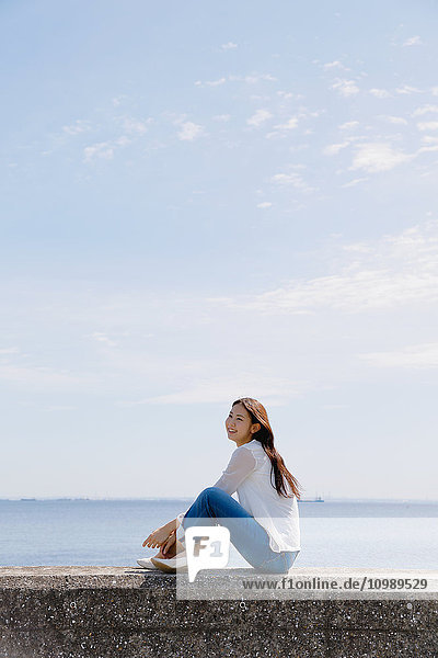 Young Japanese woman sitting on concrete wall by the sea