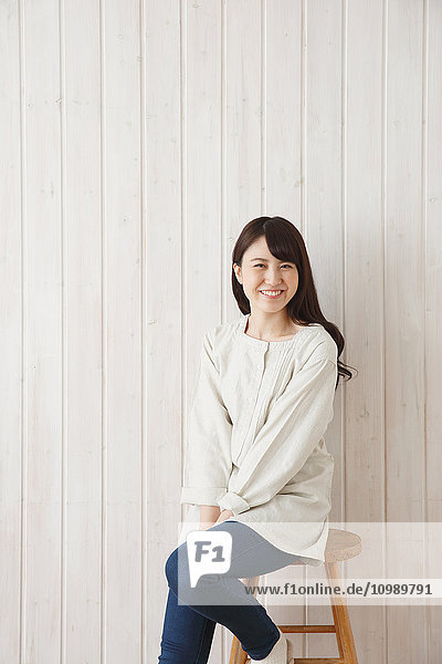 Young Japanese woman against wooden wall