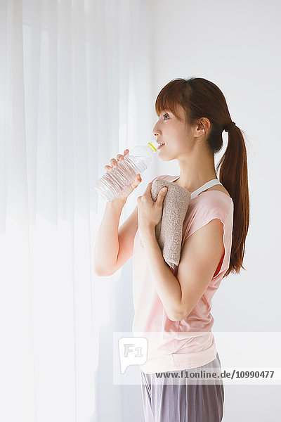 Young Japanese woman drinking water after practicing yoga