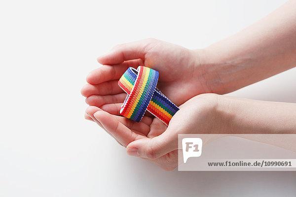 Hands holding rainbow wristbands
