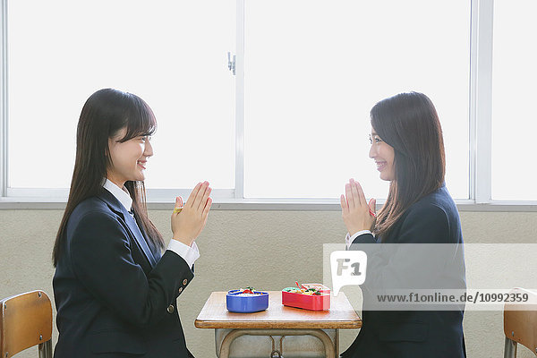 Japanese high-school students having bento in classroom