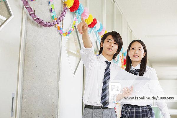 Japanese high-school students in decorated school corridor