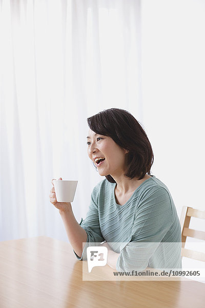 Senior Japanese woman having coffee in the living room