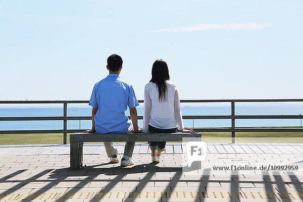 Young Japanese couple sitting on a bench by the sea