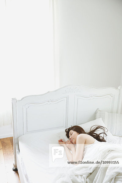 Young attractive Japanese woman sleeping in bed