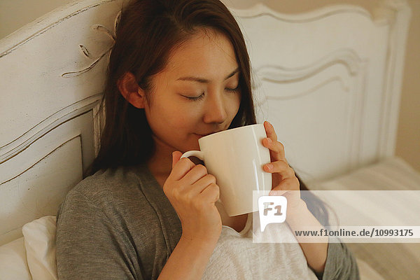 Young attractive Japanese woman drinking coffee in bed