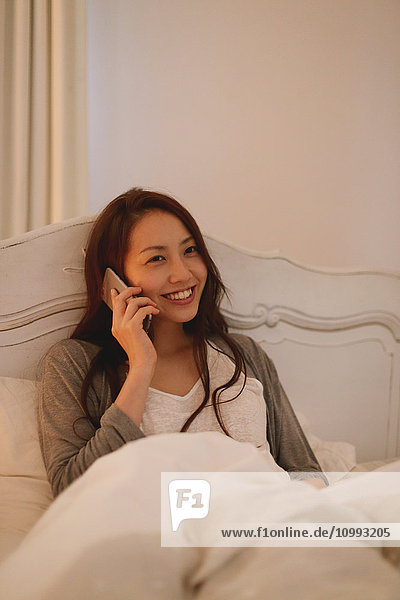Young attractive Japanese woman on the phone in bed