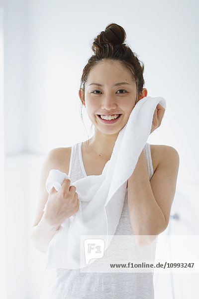 Young attractive Japanese woman wiping face with towel in the bathroom