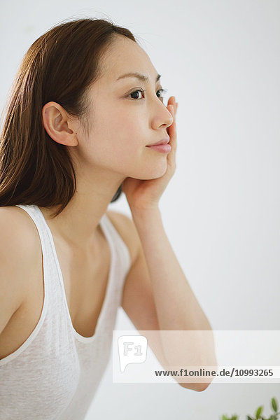 Young attractive Japanese woman doing skin care in the bathroom