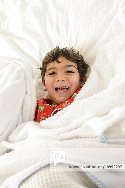 Kid playing on bed in a pijama