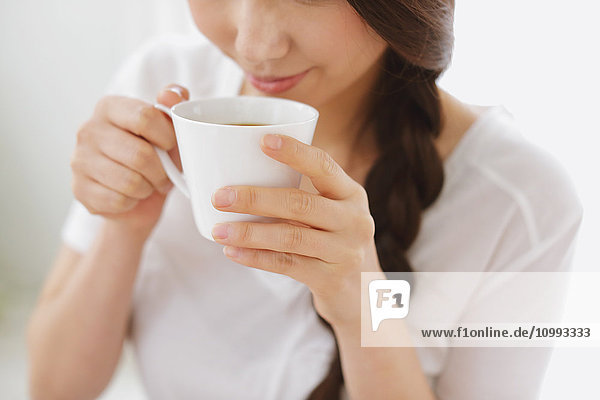 Young attractive Japanese woman having cofee at home